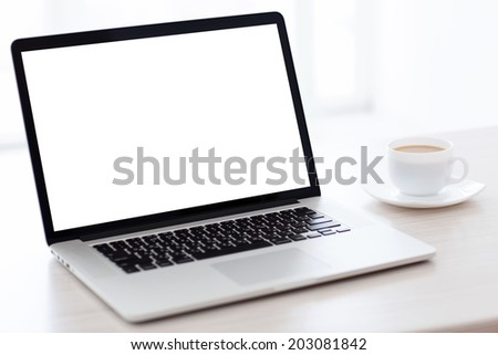 laptop computer with isolated screen is on the table with a cup of coffee in a white room - stock photo