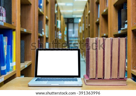 Laptop computer with old books on the wood table in library, Education concept - stock photo