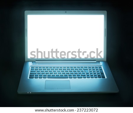 Laptop computer with screen glowing in the dark - stock photo