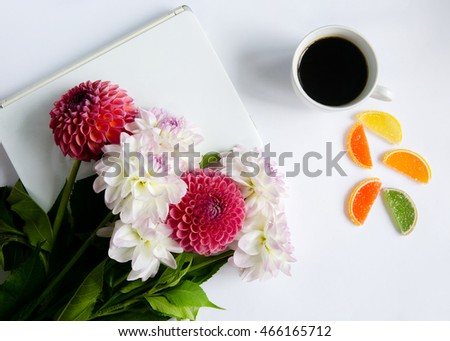 Laptop, flowers, coffee and marmalade on a white background - the workplace of a creative person