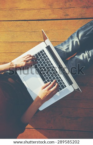 Laptop in girls hands typing and sitting on a wooden floor. View from above - stock photo