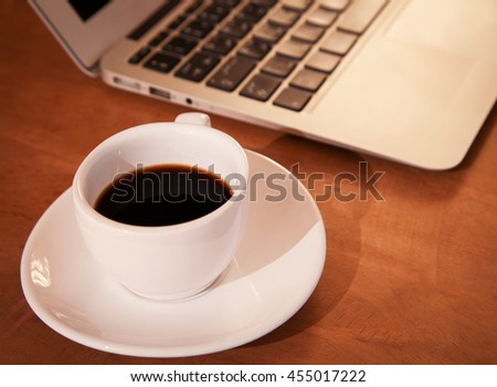 Laptop keyboard with coffee cup, wood background - arabic keyboard
