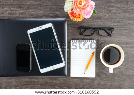 Laptop Mobile Phone and Tablet with notebook and a cup of coffee on the desk - stock photo