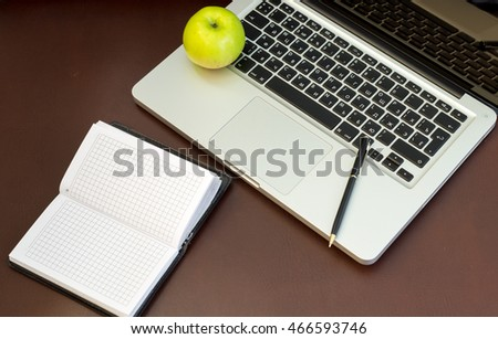 laptop, notebook and apple on background of a leather sofa