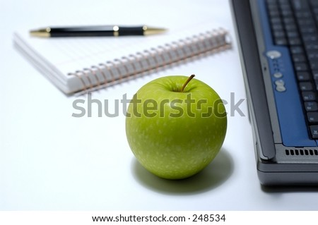 Laptop, notebook, pen and green apple on a white background. Focus on apple.