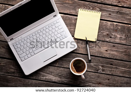 Laptop (notebook) with cup of coffee and notepad with pen on old wooden table. - stock photo