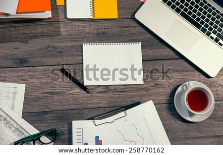Laptop, notepad, glasses and tea cup on office wooden table - stock photo