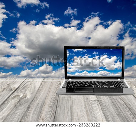 laptop on a wooden table on a background of the sky - stock photo