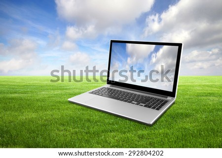 Laptop on green grass  - stock photo