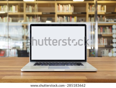 Laptop on table, on bookshelf background,blank screen,library interior - stock photo