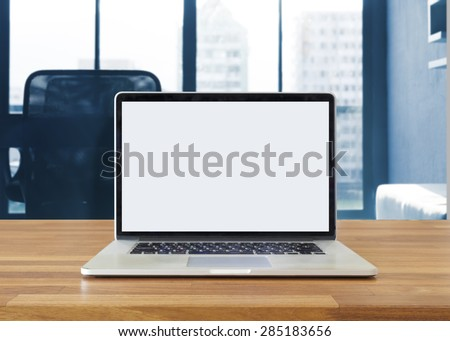 Laptop on table, on office background,blank screen - stock photo