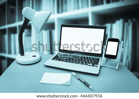 laptop on table with perspective bookshelf background