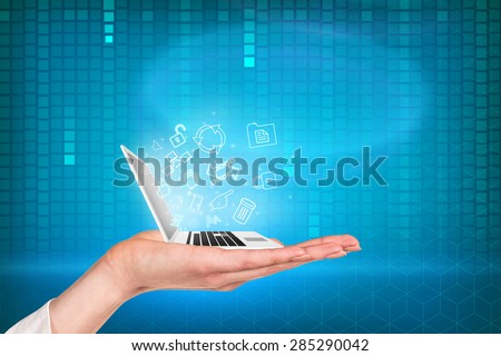Laptop on the hand with blue matrix background and symbols