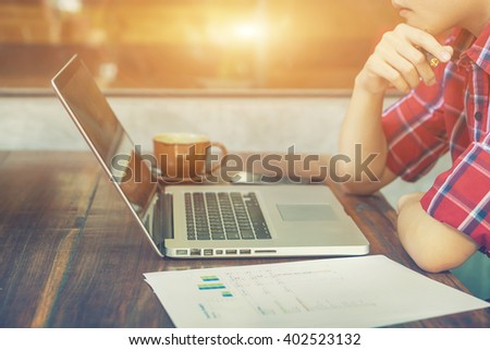 laptop on wooden table and men's hands keyboarding on laptop,male person working on net-book sitting in coffee shop indoors,male freelancer connecting internet computer,selective focus,vintage color - stock photo