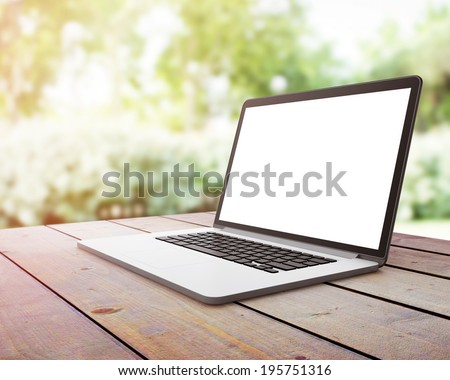 Laptop on wooden table on nature - stock photo