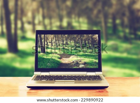 laptop over wooden table outdoors and blurred background of trees in the forest - stock photo