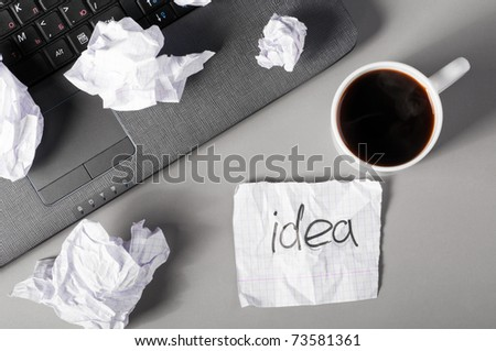 laptop, sheet of paper and crumpled wads on table. - stock photo