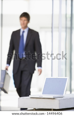 Laptop sitting in office lobby with businessman walking in - stock photo