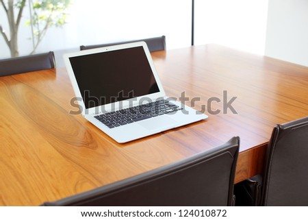 Laptop sitting on empty table