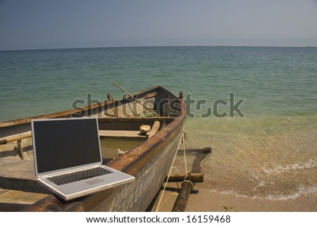 Laptop sitting on side of small fishing boat that is docked on beach - stock photo