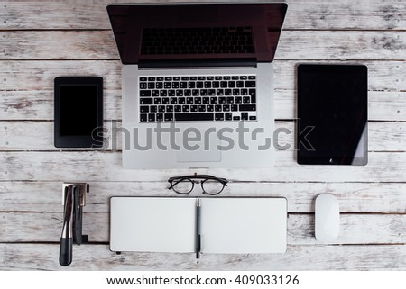 laptop surrounded office  supplies,   business and technology concept. desktop top view,perfect workplace, stamping device - stock photo