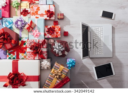 Laptop, tablet and smart phone on a desk with plenty of colorful gifts, celebrations and Christmas concept, top view - stock photo