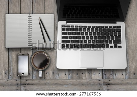 Laptop tablet computer with smartphone   and cup of coffee on old wooden desk. Simple workspace or coffee break with web surfing. - stock photo