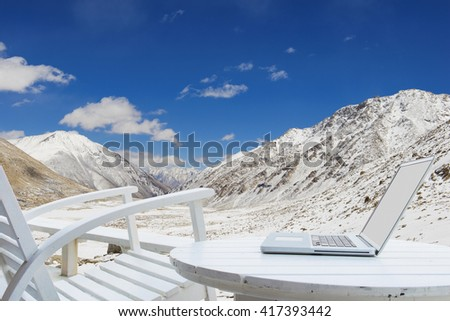 Laptop using wireless technology on high mountain with snow - stock photo