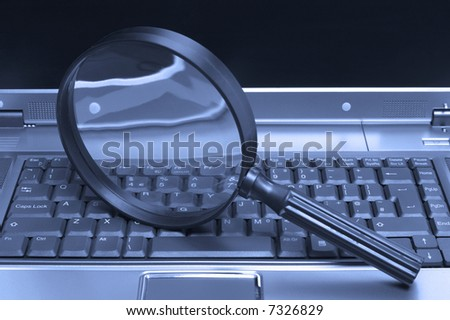 Laptop with a magnifying glass, concept of online security and investigation. - stock photo