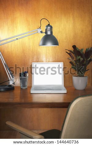 Laptop with blank screen and other items on desk with chair - stock photo