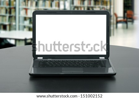 laptop with blank screen on the table in library - stock photo