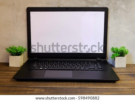 laptop with blank screen on the wood table and loft wall