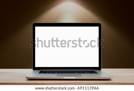 Laptop with blank screen on wood table and down lighht background. Clipping path include.