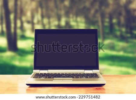 laptop with blank screen over wooden table outdoors and blurred background of trees in the forest - stock photo