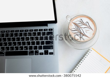 Laptop with coffee cup and notebook on marble table. - stock photo