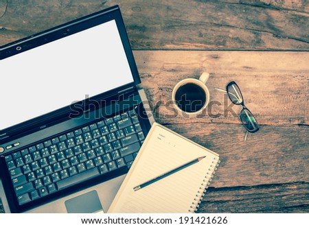 Laptop with coffee cup on old wooden table. - stock photo
