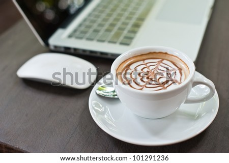 Laptop with coffee cup on wood table - stock photo