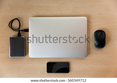Laptop with external hard drive, mouse and smart phone on wood. View from above. - stock photo