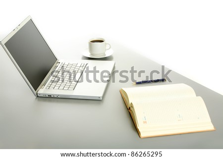 laptop with fresh cup of coffee and notebook.