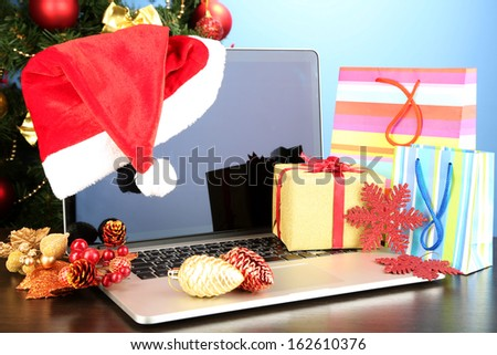 Laptop with gifts on table on blue background - stock photo