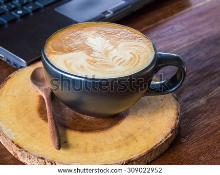 Laptop with latte art coffee cup on old wooden table in  coffee shop - stock photo