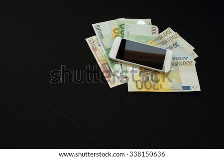 laptop with money on black background - stock photo