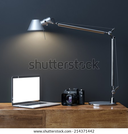 Laptop With Photo Camera Under The Lamp In Interior Room - stock photo