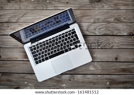 laptop (with russian keyboard) on old wooden desk - stock photo