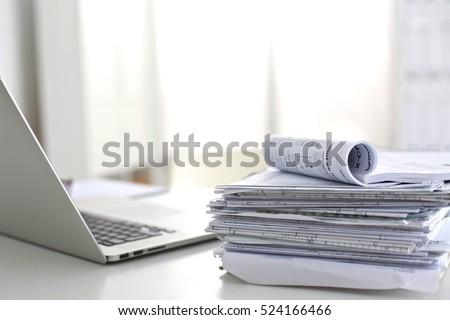 Laptop with stack of folders on table  white background