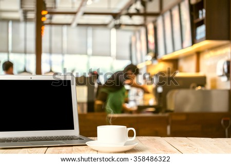 Laptop with tablet, pen and a cup of fresh coffee latte art on wooden table in coffee shop - stock photo