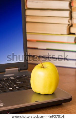 laptop with yellow apple on books background - stock photo