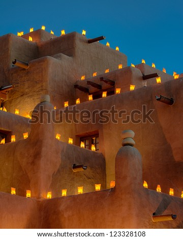 Large adobe building decorated with luminaria for the holidays
