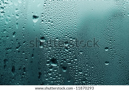 Large and fine water drops on glass. - stock photo