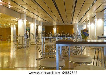 Large and new conference/meeting  room with white stools and tables - stock photo